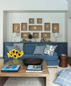 Stunning cottage living room with white beadboard walls framing collection of white coral in shadow boxes over custom blue cabinets doubling as bar. Nantucket, Blue Tufted Sofa, Les Hamptons, Bead Board Walls, White Beadboard, Cottage Living Rooms, Living Spaces, Blue Cabinets, Beach House Decor
