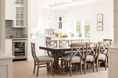 A Restoration Hardware Salvaged Wood & Weathered Concrete X-Base Rectangular Dining Table sits on blond wood floors surrounded by x-back dining chairs and is positioned in front of a wet bar fitted with white shaker cabinets and a glass front mini fridge accented with gray mosaic backsplash tiles and glass front upper cabinets.