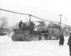 A Pershing tank tows a Cleveland-Berea bus south on Rocky River Drive during the 1950 Thanksgiving weekend snowstorm. The caption did not provide more information. The partly obscured sign behind the tank may indicate a Sohio station that once existed near Puritas.