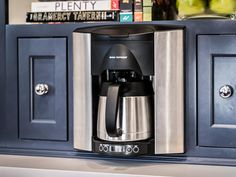 Coffee is made easy with a stainless steel coffee machine that's programmable to brew a pot before homeowners wake up. A built-in nook for the coffee maker maximizes counter space. Built In Coffee Maker, Drip Coffee Maker, Stainless Steel Coffee Maker, Need Coffee, Plaster Walls, Spanish House, Family Kitchen, Wood Beams, Coffee Machine