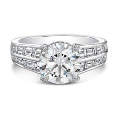 FM Baguette Ring - Round forevermark diamond accented with round melee diamonds on a  baguette cut diamond band in platinum.