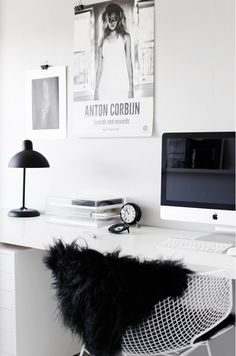 Black and white workspace with black fur throw on office chair.