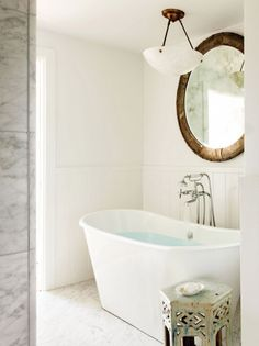 Beautiful white bathroom with gray tiles and round wood mirror