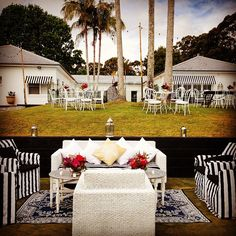 White pure linen hamptons sofas teamed with directors chairs clothed in black and white striped covers, blue and white mats and silver and white occasional tables - deluxe!