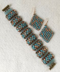 This stunning Turquoise and Gold Bracelet and Earrings set is bead woven, using Czech SuperDuo glass beads in Apollo Gold and Turquoise/Gold. It is done in a wave design, adding in Japanese Bronze seed beads and a Metallic Copper Luster. The bracelet clasp is in Antique Bronze. They give the design a rich earthy look, mixed with the beautiful pop of turquoise. The earrings use the same materials, and are made to match in a diamond shape.  The bracelet measures 7 inches in length, and is 1…