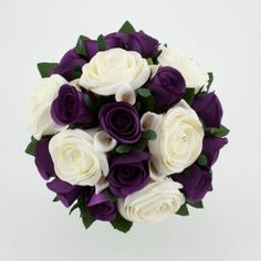 ivory roses with diamonte centre, cadbury purple roses and small white cala lilies.