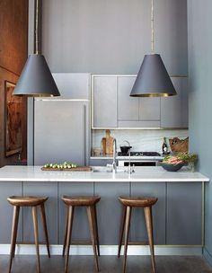 Em cozinhas totalmente abertas para a sala, armários com linhas retas, sem puxadores e com a mesma cor da parede tornam a cozinha mais discreta, o que interfere menos na decoração da sala.