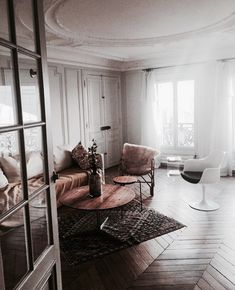 Sheer flowy curtains, solid dark wood floors, rugs, fur soft couches add a variety of textures for this space.