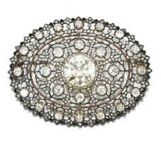 DIAMOND BROOCH, BUCCELLATI, CIRCA 1930. The oval open work plaque of lace design, set to the centre with a circular-cut diamond, accented with circular-cut and rose diamonds, signed Buccellati, case by Buccellati. [Cross posted from Buceellati]