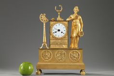 A gilt and chiseled bronze figural mantel clock richly decorated with literary, artistic and scientific symbols. The white enamel dial is in a case cast as shelves of books surmounted...