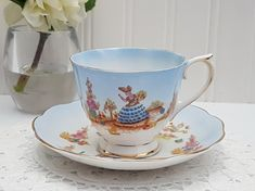 "A pretty teacup set by Royal Albert in the ""Dainty Dinah"" pattern in the harder to find blue ombre. The teacup and saucer are decorated with a dainty lady in a garden with the opposing side having a floral arbour, and clusters of flowers surrounding. Both pieces are trimmed in gold. This pattern was released in 1927 with the back stamp ""Crown China"" to 1935. This teacup is stamped with ""Bone China"" and was released in the 1940's."