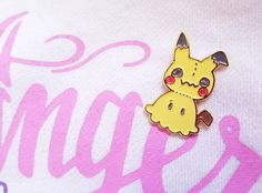 THESE ARE READY TO SHIP!  Little Mimikyu the not-Pikachu, not-spook is ready to come with you on your journey to be a Pokemon master, riding on your jacket or backpack or hat or wherever it is you choose to stick your enamel pins (no judgement).  Each pin is made of high-quality soft enamel (inlaid paint), with enamel coloring and gold plating, and has a butterfly clip backing. They stand 33mm high (~1.2). The ship on custom-made backing cards in cellophane wrapping!  Show Mimikyu some love