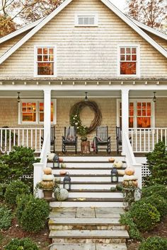 Sometimes, more is more! This front porch in Connecticut spares no expense, with a giant wreath, an assortment of gourds, and cozy throw blankets to boot.