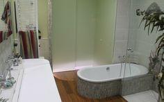 rénovation de salle de bain réalisée par les Bains & Cuisines d'Alexandre La salle de bains de plein pied dispose d'une douche à l'italienne avec des parois en verre sur mesure allant du sol au plafond. La baignoire en acier bénéficie elle d'un habillage en petit carrelage épousant son contour et qui rappelle, par son arrondi, la contre marche à proximité -  Architecte d'intérieur: Denis GILLET, Mikael TAILLEUR - Coordinateur de travaux: Denis GILLET
