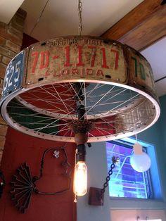 lampara con ruedas de bici y patentes viejas
