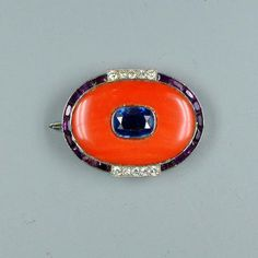 A coral, sapphire and amethyst brooch by Cartier