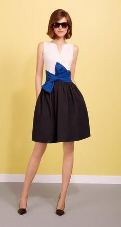 Robe bi-matière sans manches en jersey de coton et popeline papier. Haut en jersey de coton, bas de robe en popeline papier. Ceinture nouée à la taille, non amovible, de couleur contrastée. Fermeture zippée au dos. Longueur : 55 cm.