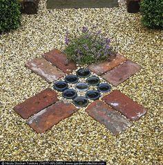 Flooring detail of brick squares enclosing upturned glass bottle bottoms, set in gravel path