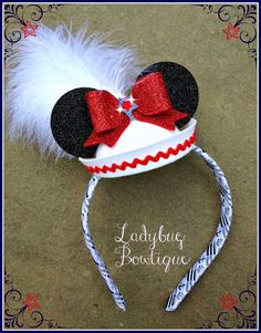 "This sailor hat is ready to cruise! Sparkle bows are placed on front AND back so they are seen coming and going! Sparkle ears and a poof of fluffy feathers complete the look. The hat is placed on a 1/2"" comfort headband that has been woven with grosgrain ribbon. Not for children under 3.  Spark..."