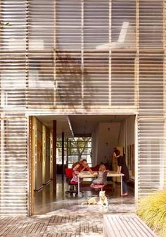 The ground floor of Andrew Dunbar and Zoee Astrakhan's house in San Francisco serves as an office for their design practice and occasionally doubles as a play area for their daughters Miika, left, and Anais. The rear facade of the house is covered in inexpensive corrugated polycarbonate panels. - Matthew Millman New York Times News Service