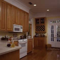 Kitchen with cabinets all the way to the impressive crown molding in Plan 024D-0061 | House Plans and More