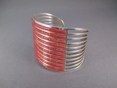 """Sterling Silver and Coral Inlay Cuff Bracelet.  Made by Zuni jewelry artists, Anson & Letitia Wallace.  10 rows of finely inlaid Coral.  Beautifully made!  Artist: Anson & Letitia Wallace Tribe: Zuni Metal: Sterling Silver Stone: Coral Length: 5 3/8"""" Width: 1 3/4"""" Opening: 1 1/8"""" https://www.fineindianart.com/product/coral-inlay-cuff-bracelet-anson-letitia-wallace/"""