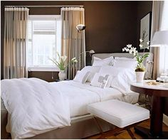 Dark brown walls with a white comforter to take the edge off
