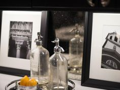 Boston photographer Matt Kalinowski was commissioned to capture zoomed-in vignettes of Boston's most popular historic sites and attractions. Framed images are paired with a mirrored tray that serves up circa-1930s seltzer bottles from Massachusetts companies GESCO Beverage and Colonial Cambridge.  #HGTVUrbanOasis