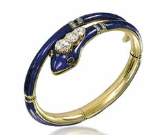 A 19TH CENTURY DIAMOND-SET SNAKE BANGLE  The sprung hinged body with blue enamel decoration and rose-cut diamond line accents, to the three stone old-cut diamond-set head with ruby cabochon eye detail, circa 1840, 21.8cm long