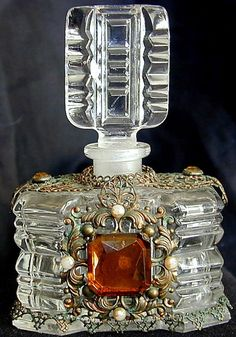"VINTAGE JEWELED CZECH PERFUME BOTTLE - A vintage perfume bottle with gilt filigree metal design and colored glass stones; 4.25""."