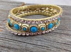 "Set of 3 Gold, Turquoise, and Rhinestone Bracelets.  This is a fun set of bracelets!  The two thinner ones are rhinestones all the way around.  The wider one (still only 1/4"") is gold-toned metal with plastic turquoise colored insets.  Stretches to fit most wrists."
