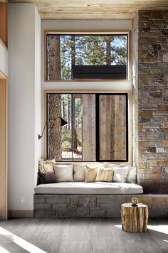 Large windows provide a view of the wooded area surrounding the home.