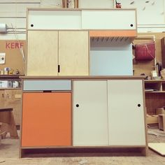 Maple plywood kitchen storage with Tangerine and Sky laminate. Not quite…