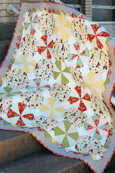 Prairie Pinwheel Baby Quilt-Made with pinwheel and snowball blocks, this generously-sized baby quilt is accented by prairie points and a sweet checked border. Finished size is 48″x56″.