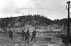 U.S. soldiers walk by a bombed out cemetery in Agana, Guam, Aug. 9, 1944. (AP Photo/Joe Rosenthal)