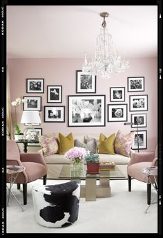 pink room with wall of black and white framed photos.