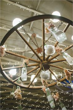 vintage wood wheel chandelier with hanging bottles and flowers | photo: www.delbarrmoradi.com