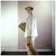 Model wearing beige silk box-top jacket over matching dress by Harvey Berin with hat by John Frederics. Circa March 1953 Photo Clifford Coffin