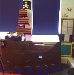 Book corner in a pirate ship- what made boys read!  I like the striped flags.