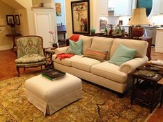 The living room comes together with a classic white sofa, colorful side chair, and complementary rug. A simple ottoman in front may one day be switched out for a larger coffee table but for now works well with a simple tray on top for drinks.