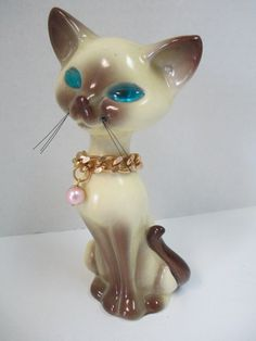 Vintage ceramic siamese cat with blue glass eyes, and black whiskers with a gold necklace figurine.
