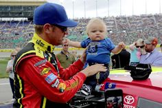 Clint Boyer stands with 7-mo-old son Cash on pit road before the start of SpngeBob Squarepants 400 at Kansas Speedway on May 9