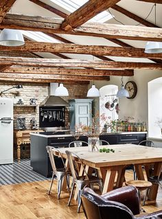 Rustic country kitchen with exposed timber ceilings and a vaulted ceiling with skylight