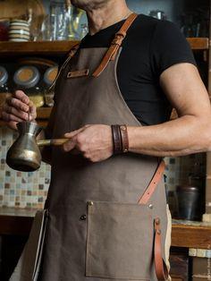 Купить или заказать Фартук мужской 'Профи 43_К' в интернет-магазине на Ярмарке Мастеров. Мужской кухонный фартук Ваш муж гурман и любит творить на кухне? Представьте его в этом стильном фартуке: - плотный 100%хлопок надежно защитит одежду от случайных брызг - кожаные ремни-лямки, перекрещивающиеся на спине, удобно лежат и не натирают шею. К тому же они отлично подчеркивают ширину мужской спины) - благодаря кобурным застежкам удобно будет настроить под себя длину ремней, а в процессе носки…