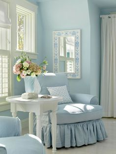 This corner of a master suite soothes with its airy palette of soft blue and white. Tiny hints of floral and stripe patterns provide just enough visual interest in the serene space. Keeping trims and embellishments to a minimum lends a grown-up touch to the pastel color scheme.