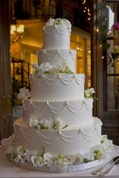 piped swags and flowers on a classic white wedding cake. magpies bakery…