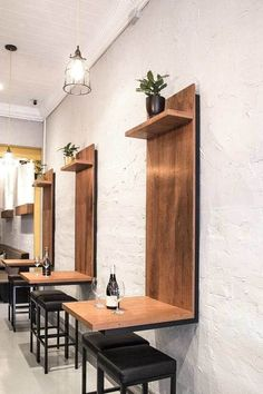 Like the extra interest the wood up the wall creates along with the warmth of the plant and wood in such an austere white scene.