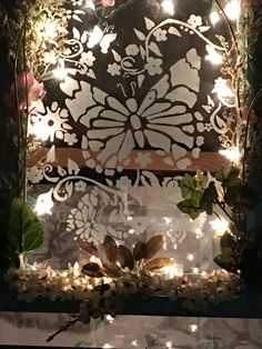 Etched butterfly on glass in picture frame lit with a strand of 20 miniature lights. Outer edge decorated with silk flowers and leaves