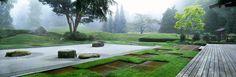 Japanese Garden, The Bloedel Reserve, Bainbridge Island, Washington. Designed byPrentice & Virginia Bloedel with Zen Garden designed by Koichi Kawana.Raked gravel, boulders, geometric pattern of grass & stone paved squares, undulating green mounds, wooden deck of Tea House.