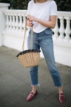 Emma Hill wears pink velvet loafers, raw hem jeans, basic white t-shirt, straw basket bag with pom poms